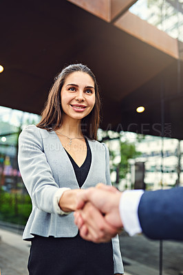 Buy stock photo Cropped shot of a beautiful young businesswoman shaking hands with an unrecognizable businessman outside