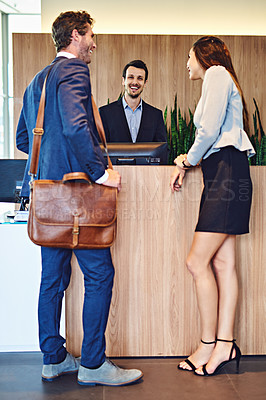 Buy stock photo Shot of businesspeople checking in at the front desk in a hotel