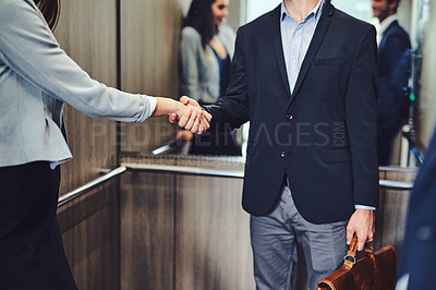 Buy stock photo Cropped shot of unrecognizable businesspeople meeting and greeting in an elevator