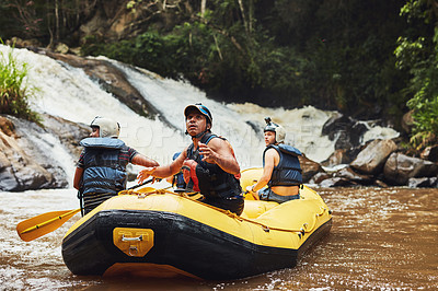 Buy stock photo Shot of a group of friends out river rafting on a sunny day