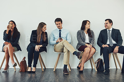 Buy stock photo Studio shot of a group of businesspeople using wireless technology while waiting in line