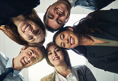 Buy stock photo Low angle shot of a group of young businesspeople huddled together in solidarity