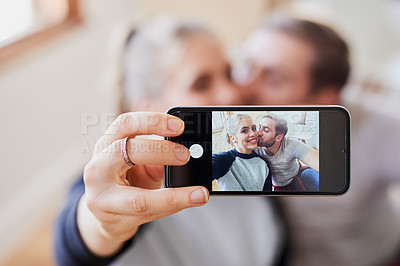 Buy stock photo Cropped shot of a happy young couple taking a picture of themselves using a cellphone in their new home