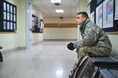 Buy stock photo Shot of a young soldier sitting on a bench in the hall of a military academy