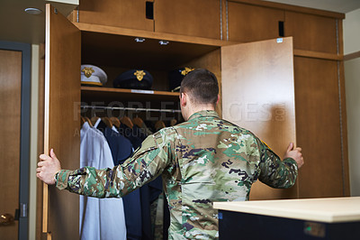 Buy stock photo Shot of a young soldier standing getting dressed in the dorms of a military academy