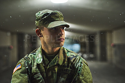 Buy stock photo Shot of a young soldier standing outside on a cold night at a military academy