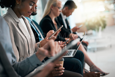 Buy stock photo Shot of a group of young businesspeople using their wireless devices while sitting in line waiting for their interviews