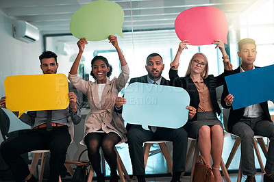 Buy stock photo Portrait of a group of young businesspeople holding up blank placards while sitting in their office