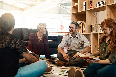 Buy stock photo Shot of a group of businesspeople having a brainstorming session while sitting on the floor