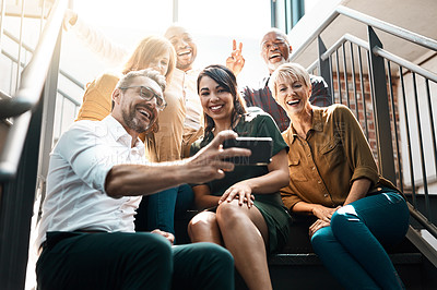Buy stock photo Cropped shot of a group of businesspeople sitting together on a stairwell