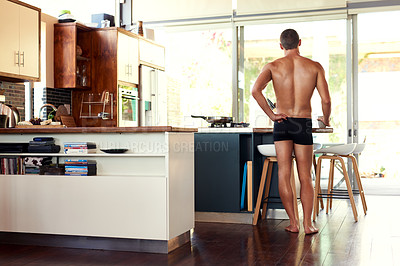 Buy stock photo Rearview shot of an unrecognizable shirtless man having a cup of coffee in the kitchen at home