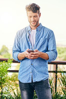 Buy stock photo Shot of a confident young man texting on his cellphone outside during the day