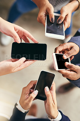 Buy stock photo High angle shot of a group of unrecognizable people browsing and texting on their cellphones while standing in a circle together