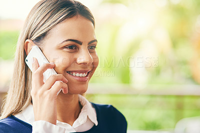 Buy stock photo Shot of a cheerful young woman talking on her cellphone while standing inside of a cafe during the day