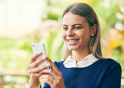 Buy stock photo Shot of a focussed young woman browsing on her cellphone while standing inside of a cafe during the day