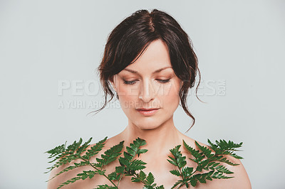 Buy stock photo Studio shot of an attractive woman posing with a plant against a gray background