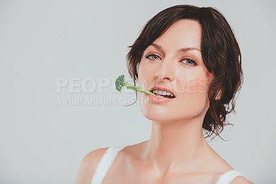 Buy stock photo Studio shot of a woman posing with broccoli against a grey background