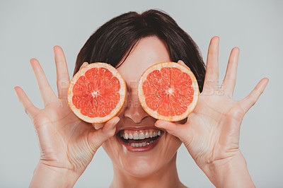 Buy stock photo Cropped shot of a woman covering her eyes with grapefruits