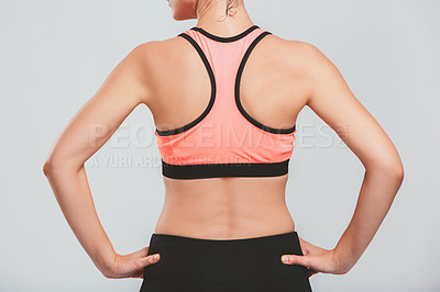 Buy stock photo Rearview shot of a sporty young woman posing against a grey background