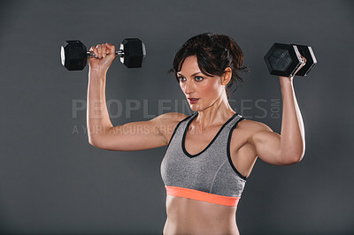 Buy stock photo Studio shot of a sporty young woman lifting weights against a grey background