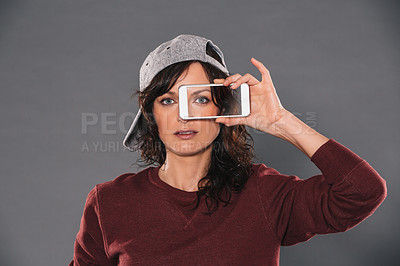 Buy stock photo Studio portrait of an attractive and trendy woman looking through a mobile phone screen against a gray background