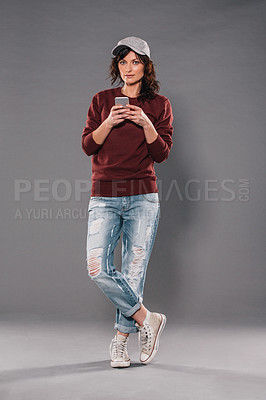 Buy stock photo Studio portrait of an attractive and trendy woman using a mobile phone against a gray background