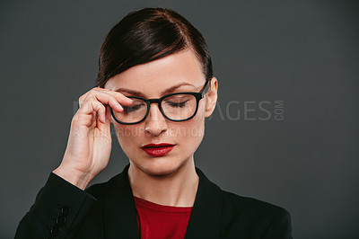 Buy stock photo Studio shot of a confident young businesswoman against a dark background