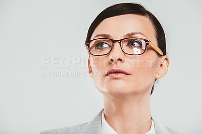 Buy stock photo Studio shot of an attractive businesswoman looking thoughtful against a gray background