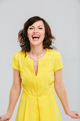 Buy stock photo Studio portrait of an attractive woman in a yellow dress posing against a gray background