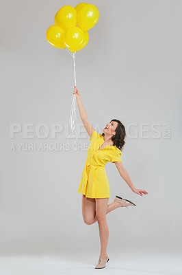 Buy stock photo Studio shot of an attractive woman in a yellow dress holding a bunch of balloons against a gray background