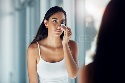 Buy stock photo Shot of a beautiful young woman cleaning her face with cotton wool in the bathroom mirror