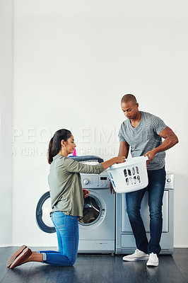Buy stock photo Shot of a young woman doing laundry at home