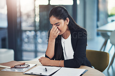 Buy stock photo Shot of a young businesswoman looking stressed out in an office
