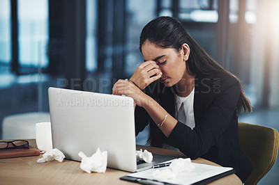 Buy stock photo Shot of a young businesswoman suffering with a headache while working in an office