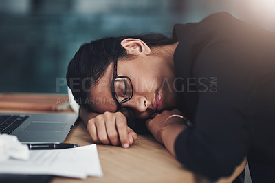 Buy stock photo Shot of a young businesswoman sleeping at her desk while working in an office