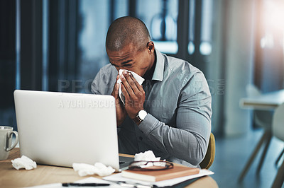 Buy stock photo Shot of a young businessman blowing his nose while working in an office