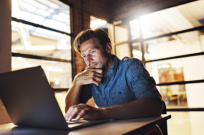 Buy stock photo Cropped shot of a handsome young male designer looking thoughtful while working late in his office