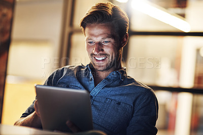 Buy stock photo Cropped shot of a handsome young male designer looking pleased while working late in his office