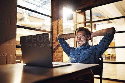 Buy stock photo Cropped shot of a handsome young male designer looking relaxed while working late in his office