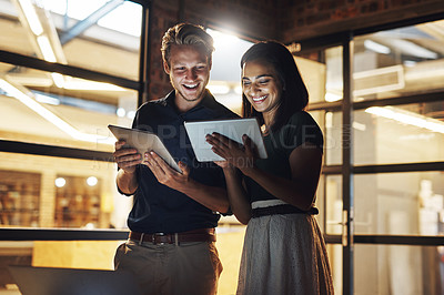 Buy stock photo Cropped shot of two young designer using their digital tablets while working late in the office