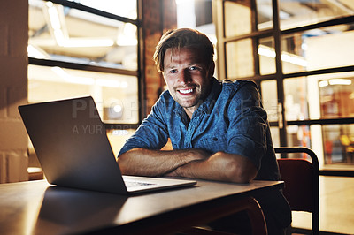 Buy stock photo Cropped portrait of a handsome young male designer looking pleased while working late in his office