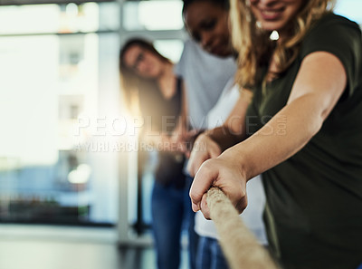 Buy stock photo Shot of a group of young businesspeople pulling on a rope in a game of tug of war
