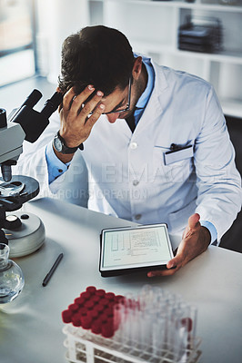 Buy stock photo Shot of a scientist looking stressed out while working in a lab