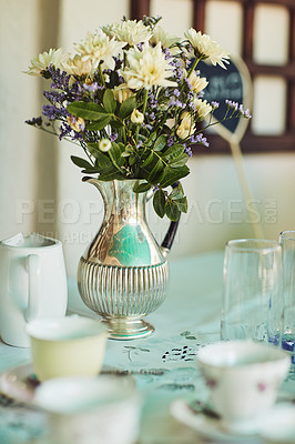 Buy stock photo Shot of a metal vase filled with flowers on a table at a tea party inside