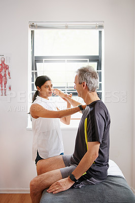 Buy stock photo Shot of a physiotherapist doing arm exercises with her patient