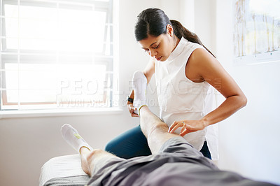 Buy stock photo Shot of a physiotherapist doing leg exercises with her patient