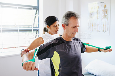 Buy stock photo Shot of a mature man using resistance bands with the help of a physical therapist