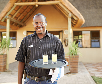 Buy stock photo Portrait of a young man on his way to serve guests drinks at a resort in nature