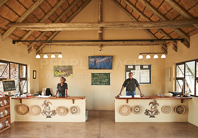 Buy stock photo Shot of the front desk clerks at a resort in nature