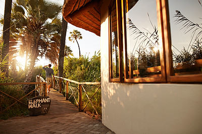 Buy stock photo Rearview shot of an unrecognizable man walking on a bridge at a resort in nature